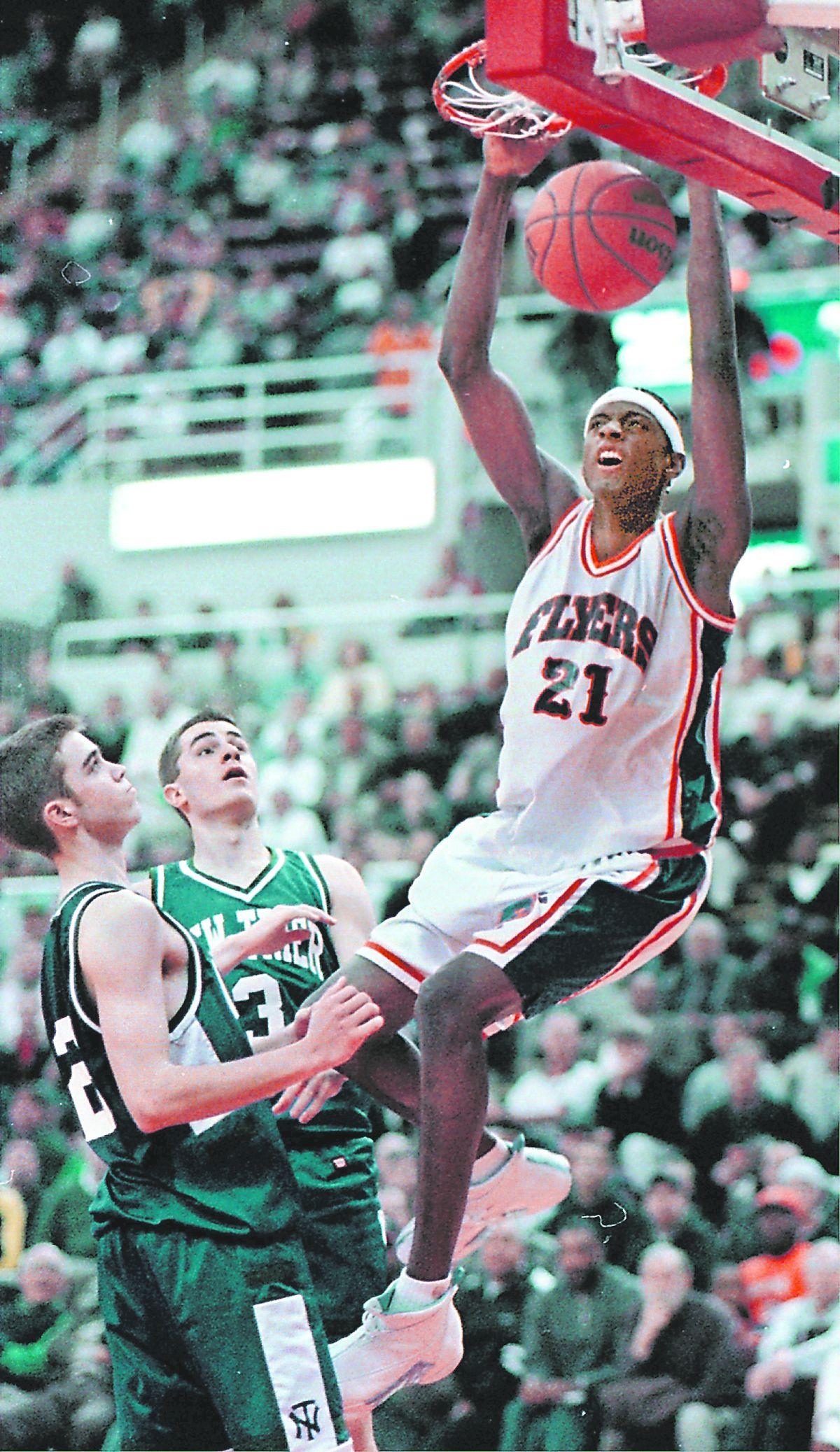 East St. Louis center Darius Miles dunks against New Trier.