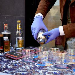 Matthias Laudico, a part-time employee at Spirited Away, pours samples for the sidewalk tasting at Spirited Away, an alcohol-free bottle shop, in the Lower East Side of Manhattan in New York on Saturday, March 13, 2021. The shop is devoted to everything needed to make alcohol-free cocktails.