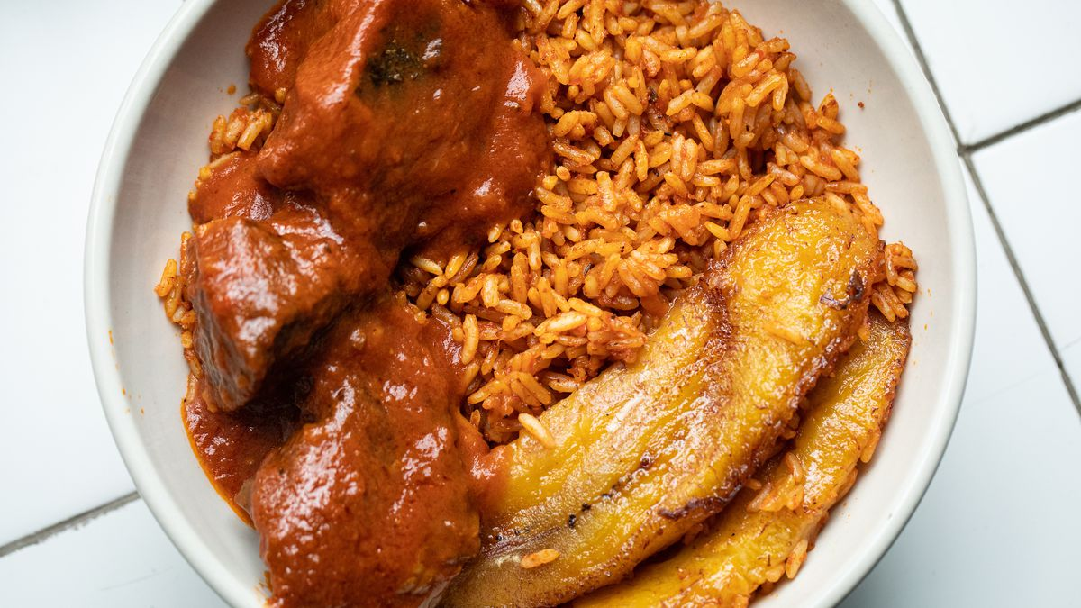 Jollof rice, stewed beef, and plantains in a white bowl, as seen from above.