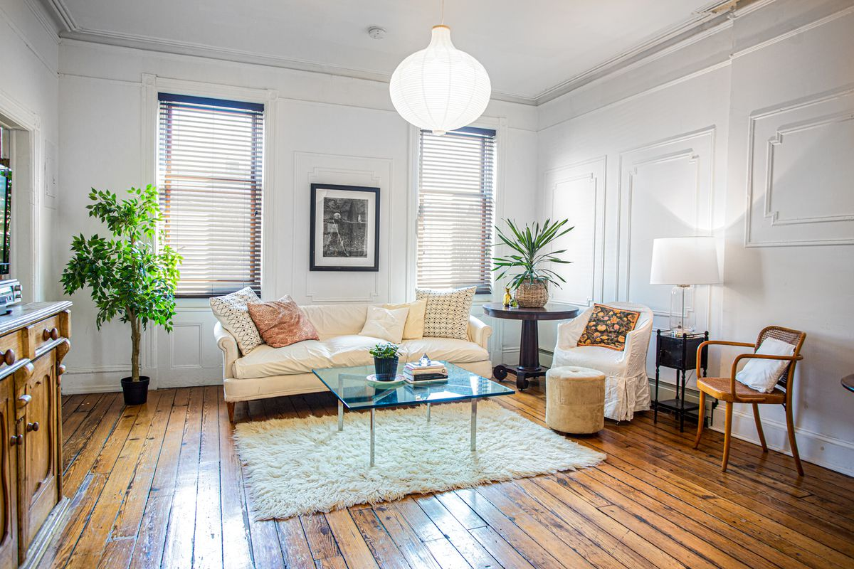 A living area with hardwood floors, a beige couch, two windows, a glass coffee table, and plaster moldings.