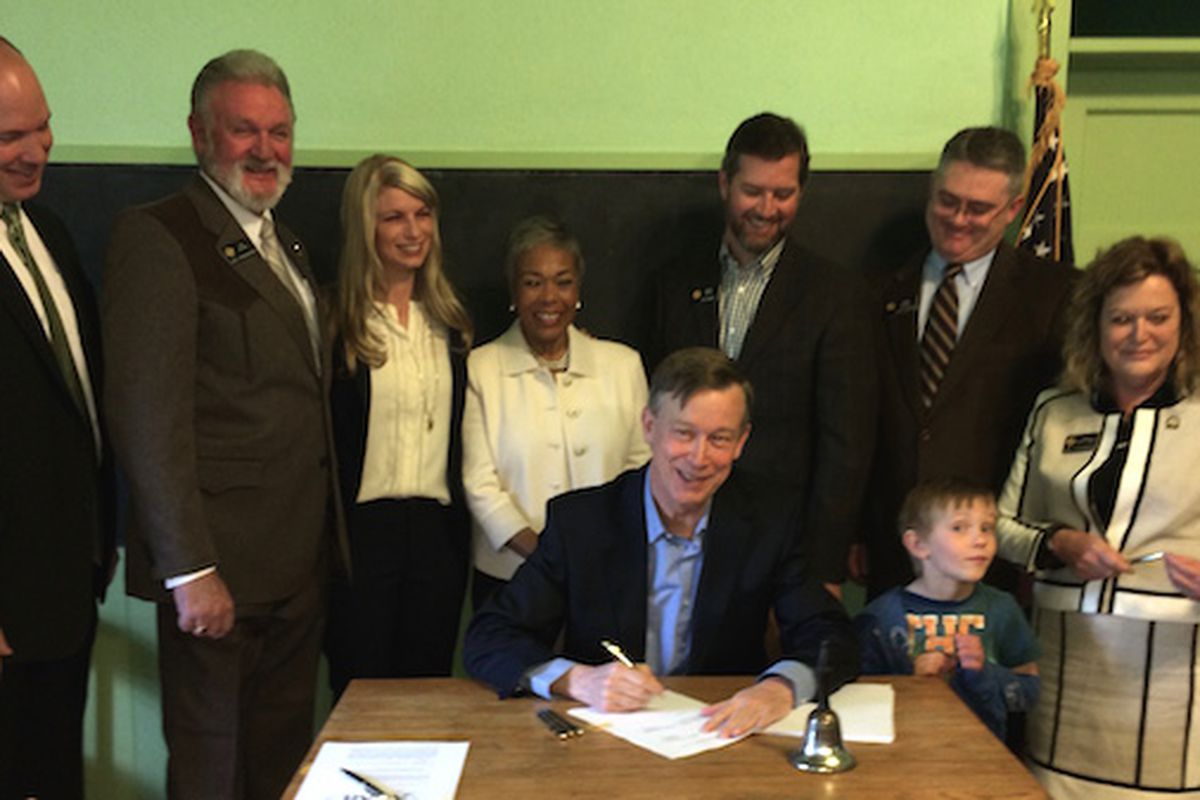 Gov. John Hickenlooper signs a test bill flanked (L-R) by Reps. Kevin Priola, Jim Wilson, Brittany Pettersen, Janet Buckner (wife of Rep. John Buckner), Sens. Andy Kerr and Chris Holbert and Rep. Tracy Kraft-Tharp. Kerr's son Griffin mugs for the cameras.