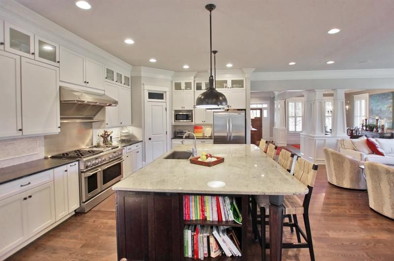 A large kitchen with a huge white marble island.