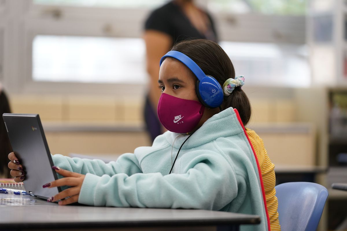 Girl wearing a mask works on her laptop at a learning center.