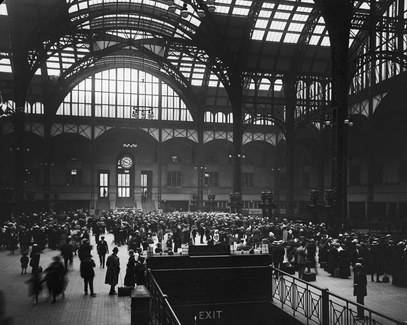 A historic black and white image of a train station. Many people walk around underneath large ornate ceilings.