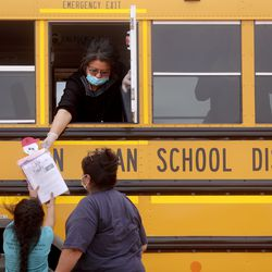 Cara Luna, Tse'bii'nidzisgai Elementary School fourth grade teacher, hands homework to second grader Chloe Benally from a school bus that delivers food and homework two days a week while schools are closed during the COVID-19 pandemic in Oljato-Monument Valley, San Juan County, on Thursday, April 30, 2020. The Navajo Nation has one of the highest per capita COVID-19 infection rates in the country.