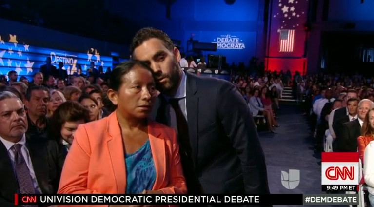 A reporter translates the Democratic candidates' response in a debate to a Spanish-speaking woman during the Univision debate.