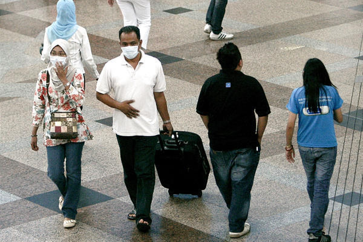 Passengers wearing masks as a precaution against swine flu walk at a terminal in Kuala Lumpur, Malaysia, Wednesday. Malaysia's health ministry on Wednesday has confirmed  three swine flu-related deaths on Monday, the highest number so far in a single day.