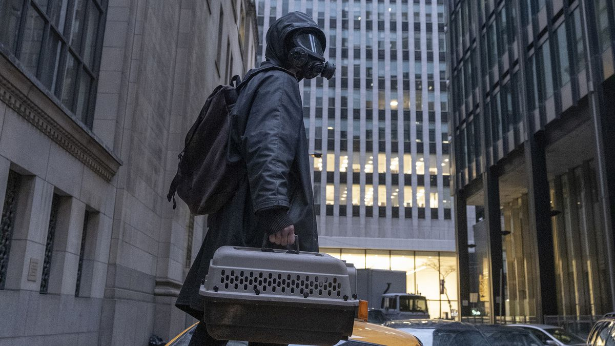 Yorick (Ben Schnetzer) standing on an abandoned taxi, wearing a poncho and gas mask and holding an animal carrier, in Y: The Last Man