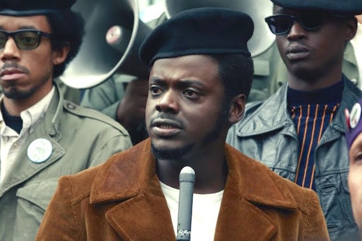 A group of Black Panthers in berets stand around Hampton, who speaks into a microphone.