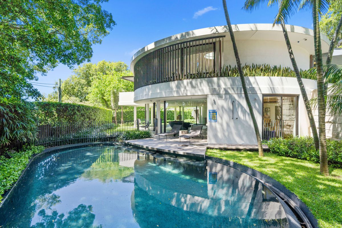 White circular house with lush garden and pool.