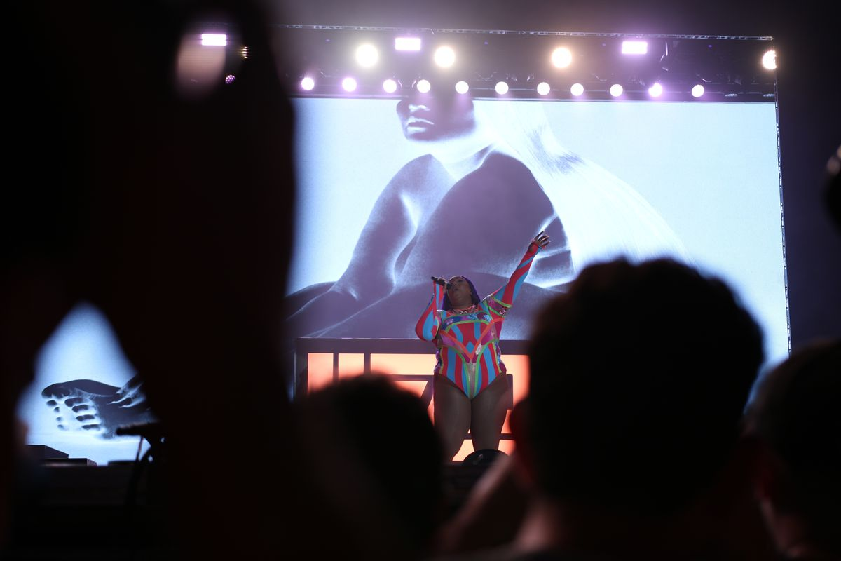 Lizzo belts out lyrics wearing a colorful leotard in front of a blown-up image of her album cover.