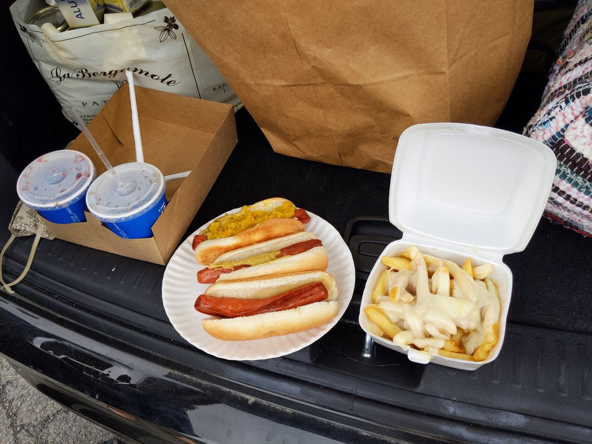Hot dogs, carbonated beverages, and disco fries on a tailgate.