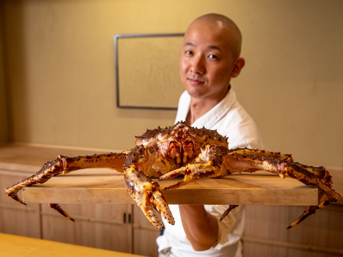 Chef Nozomu Abe stands behind the sushi bar with a giant live king crab
