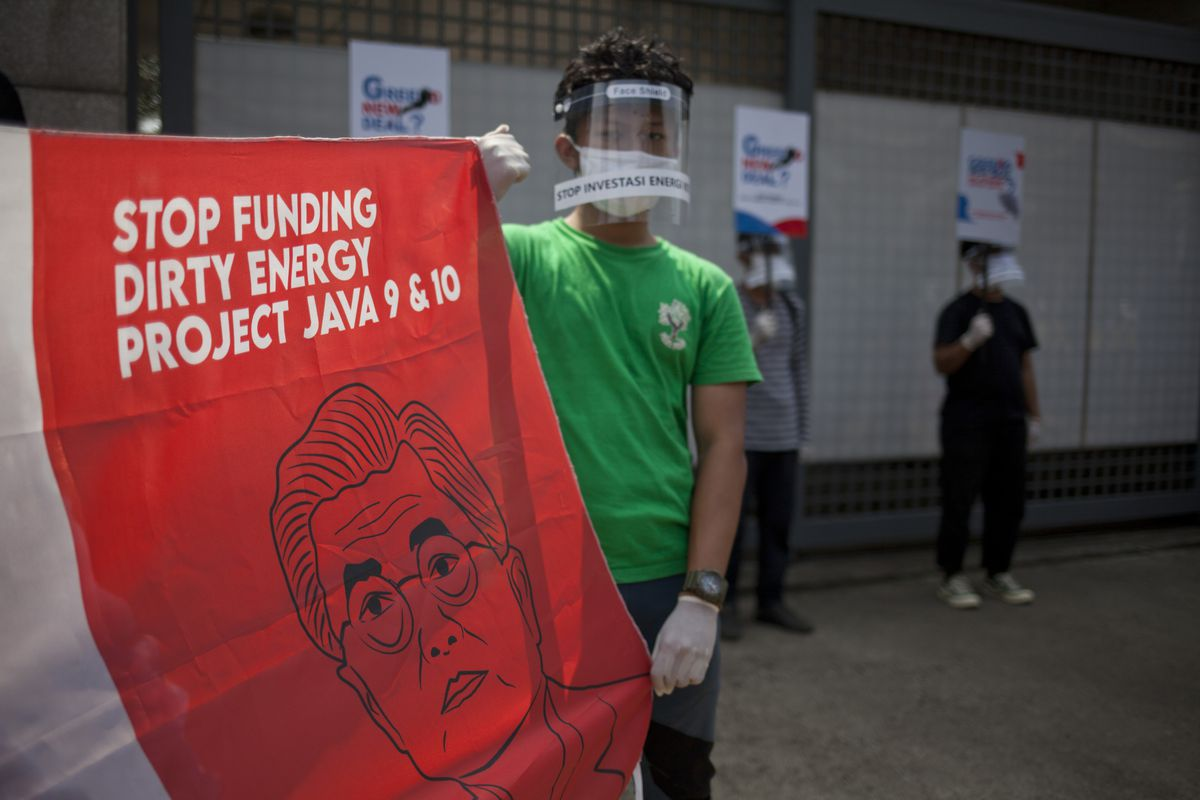 """Environmental activist is seen wearing a face shield while protesting coal power by holding a banner that reads, """"Stop funding dirty energy. Project Java 9 & 10."""""""
