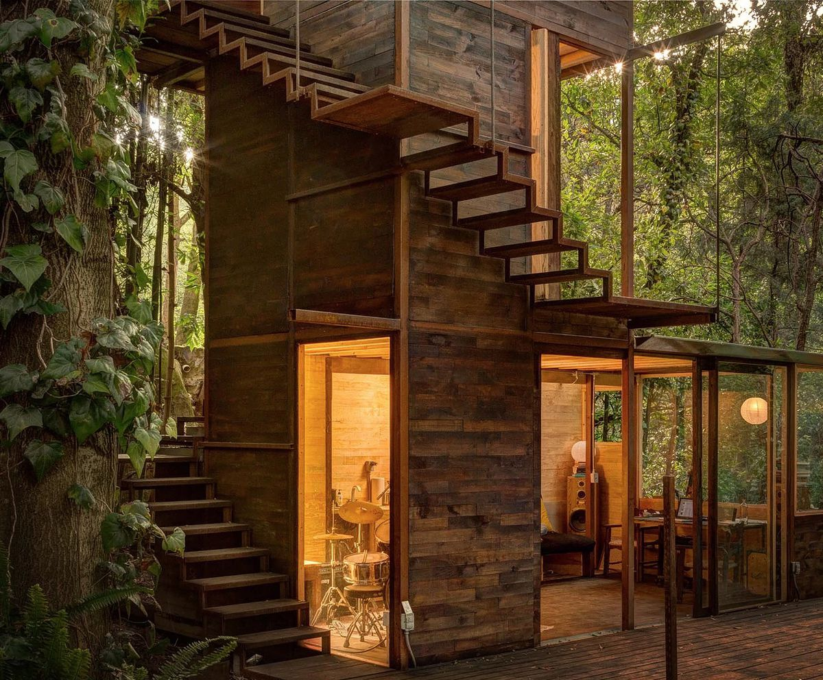 A staircase wraps around a wood treehouse in a forest.