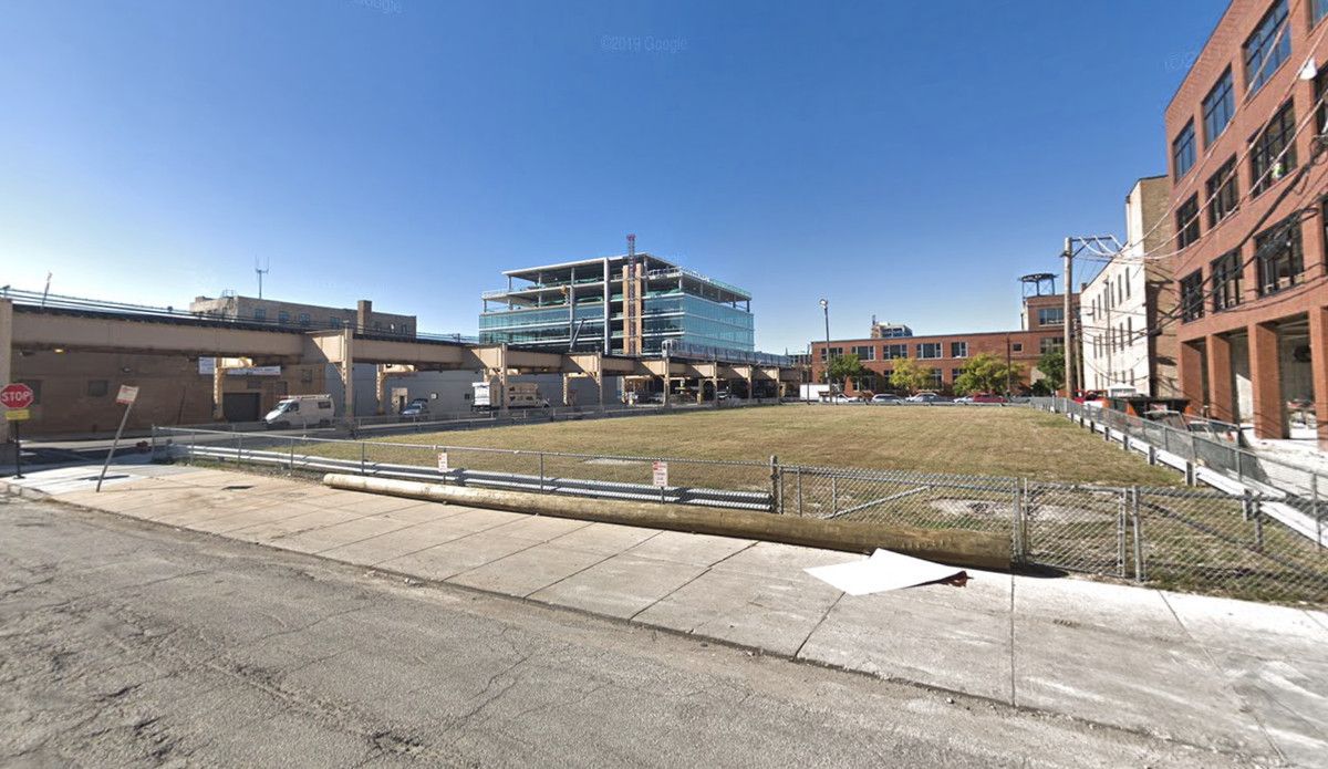 A street-level view of a grassy vacant lot that reaches across an entire city block. It's surrounded by brick loft buildings and elevated train tracks and a glassy office buildings are visible in the distance.