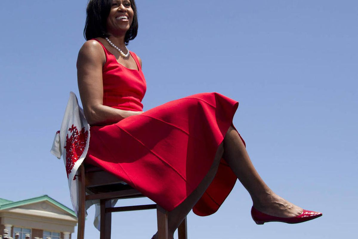 First lady Michelle Obama sits on stage as President Barack Obama speaks to troops, veterans and military families at the Third Infantry Division Headquarters, Friday, April 27, 2012, at Fort Stewart, Ga.