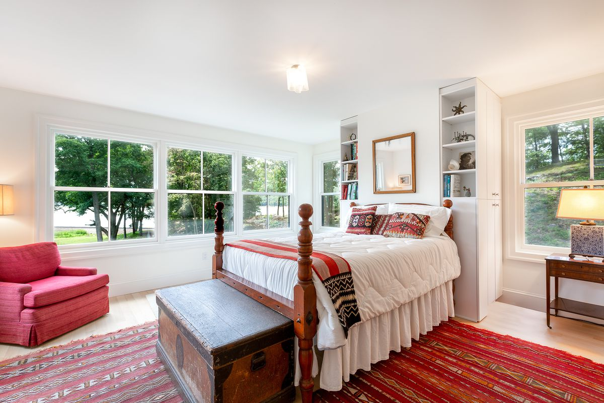 A bedroom features all-white walls, a four-poster bed with white linens and red accents, a red rug, and a chest of drawers at the foot of the bed.