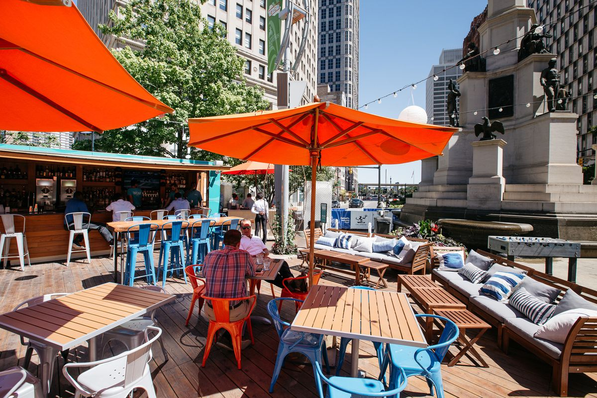 outdoor shipping container restaurant with tables and umbrellas