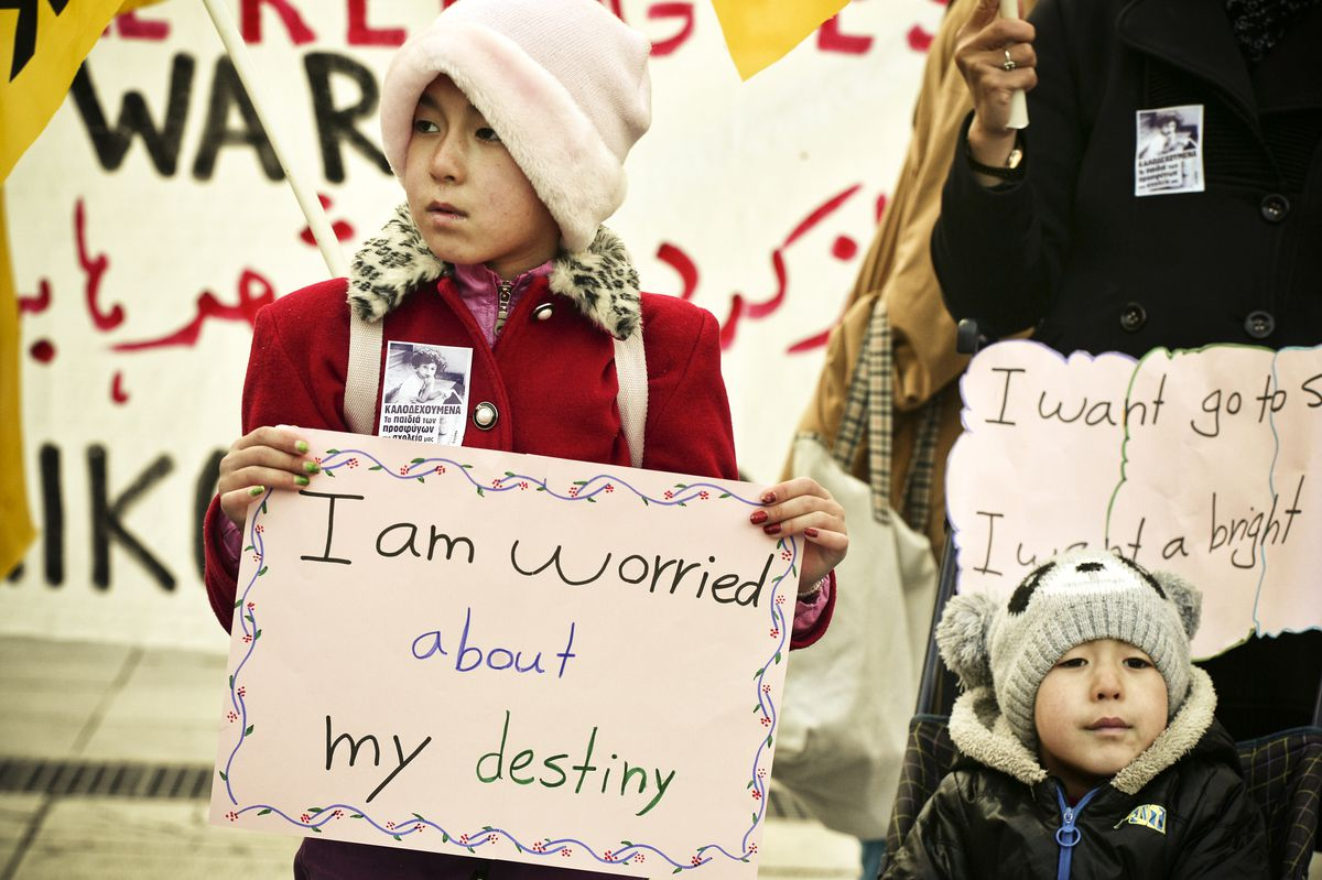 A child carries a sign as migrants and refugees demonstrate in Athens on January 21, 2017, in solidarity with the Women's March on Washington, one day after the inauguration of Donald Trump as US President.