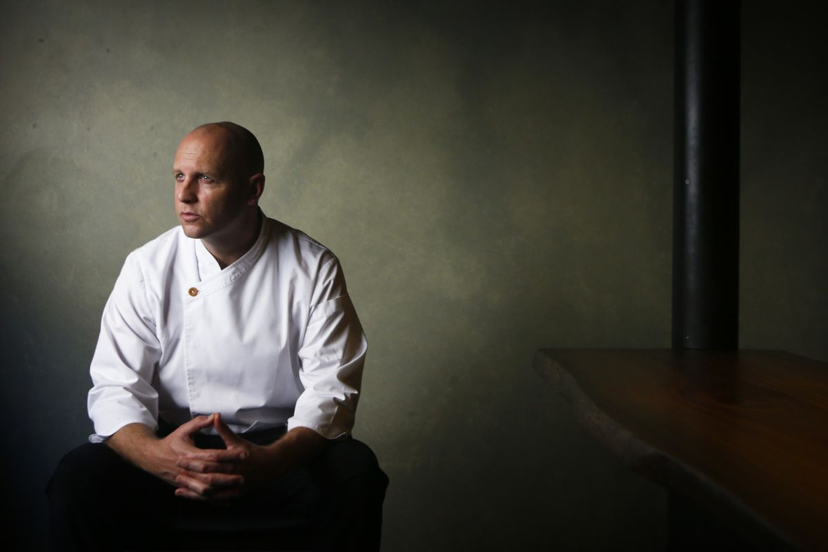 A chef looks out of a window while wearing whites in a semi-dark room.