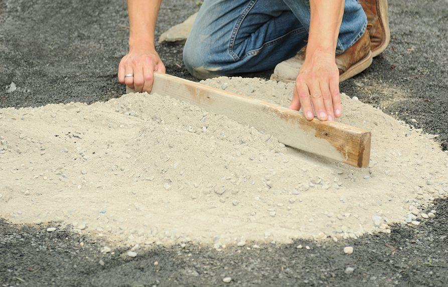 Person Preps Pebble Mosaic Site On Stone Dust