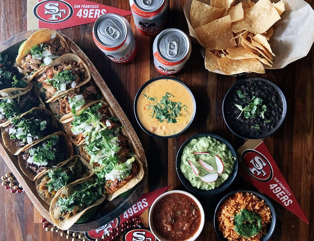A spread of tacos, bean dip, and queso at Tacolicious