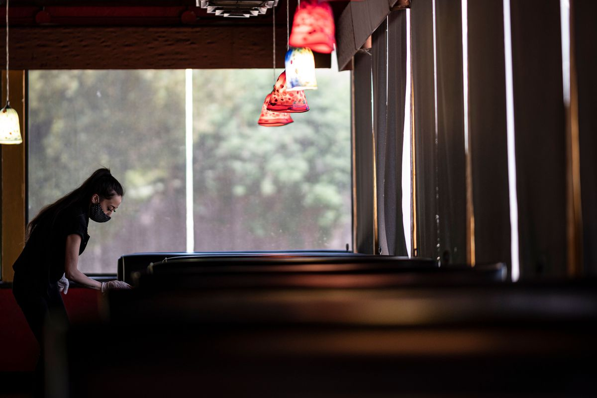 A waitress wiping down a table wearing a mask.