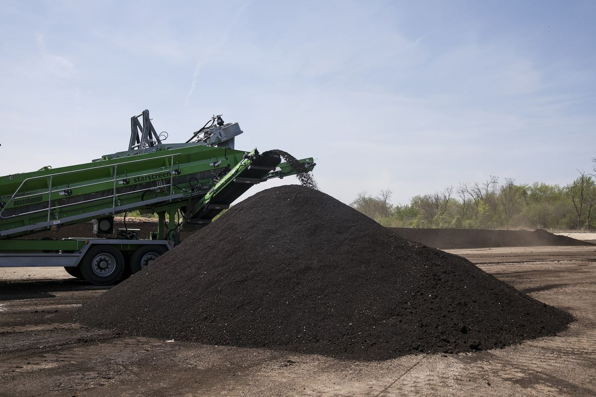 A compost screener removes larger pieces of woodchips, which are used as a bulking agent for composting with biosolids in open windrows, from finished compost at the Metropolitan Water Reclamation District.   Ashlee Rezin/Sun-Times
