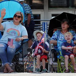Spectators wave flags during the Days of '47 Parade in Salt Lake City on Friday, July 23, 2021.