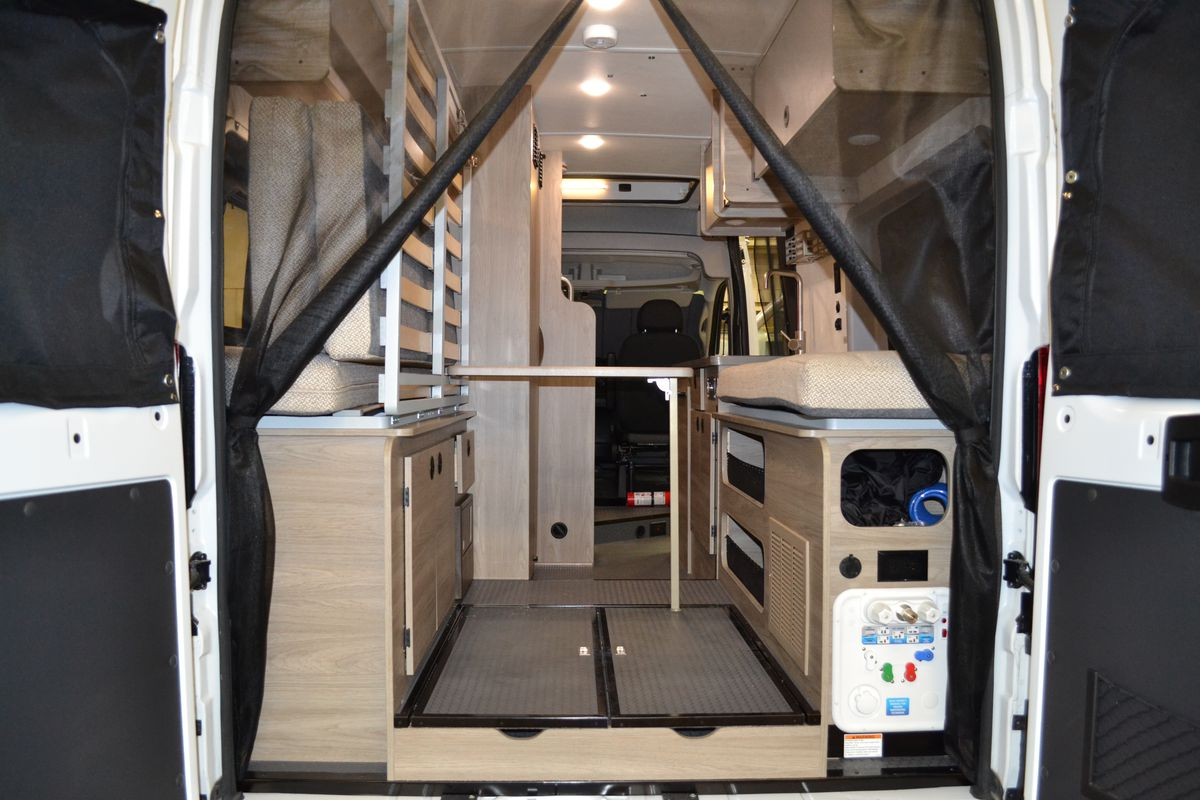 The rear look inside a white camper van. A bug netting is open and inside you can see a bench seat, folded up Murphy Bed, and table.