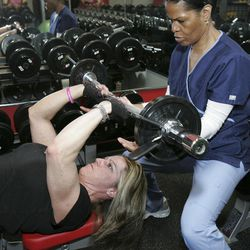 ADVANCE FOR USE SUNDAY, APRIL 22 AND THEREAFTER - In this photo taken April 9, 2012, Cindi Johnson is spotted by her personal assistant, Demetria Isabell, while working out at Premier Fitness in Rockford, Ill. Johnson was diagnosed in 2005 with multiple sclerosis, myelopathy and a degenerative disc disease. Because of her limited mobility, she uses a wheelchair. She is preparing to compete in the NPC Grand Prix Natural, Bodybuilding, Figure, Physique, Bikini & Wheelchair Championships to be held in Rockford in May.