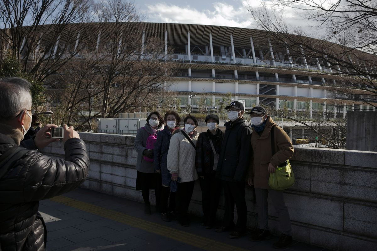 Tourists wear masks as they pause for photos in front of the New National Stadium in Tokyo.