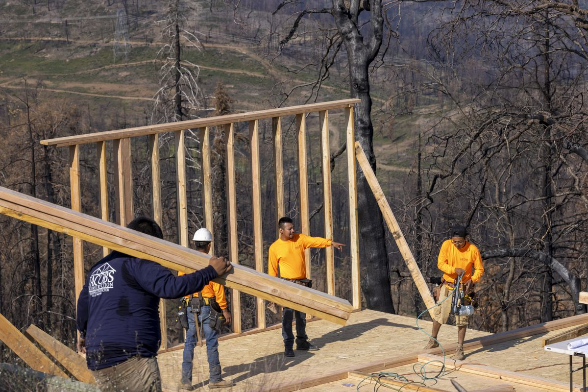 Workers rebuild a house that was destroyed by the Creek Fire, which began on September 4, 2020, and was fully contained on December 24.