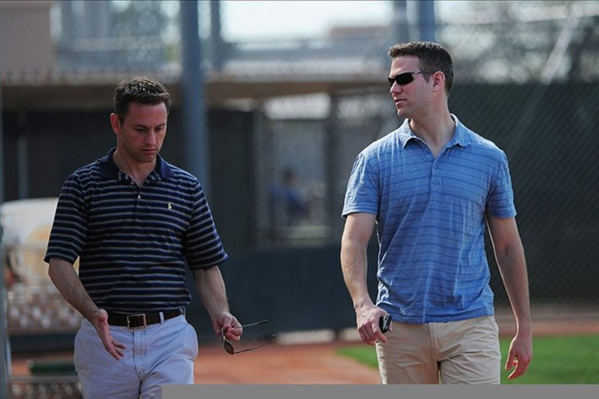 February 23, 2012; Mesa, AZ, USA; Chicago Cubs general manager Jed Hoyer (left) talks to president Theo Epstein (right) during spring training at Fitch Park. Mandatory Credit: Kyle Terada-US PRESSWIRE