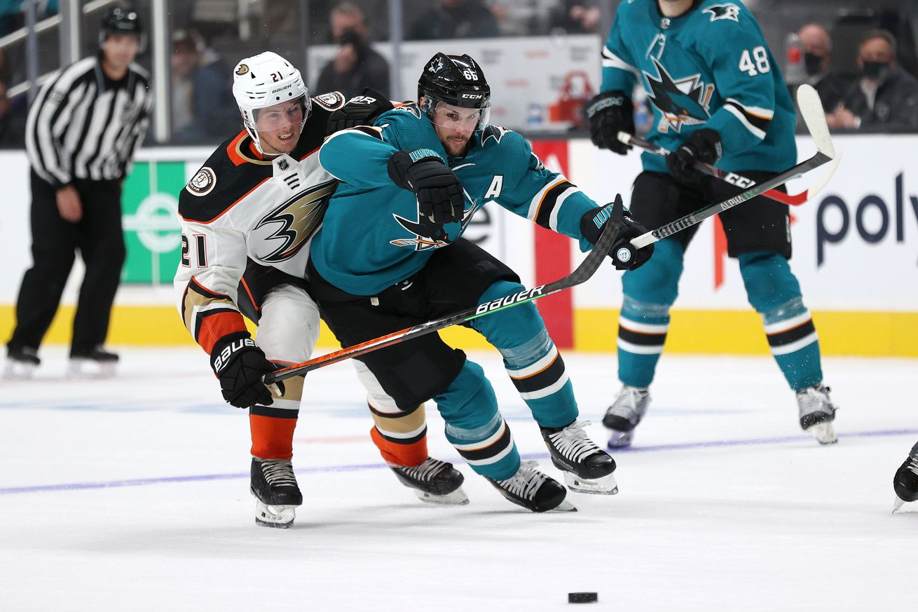 Erik Karlsson #65 of the San Jose Sharks and Isac Lundestrom #21 of the Anaheim Ducks go for the puck at SAP Center on October 04, 2021 in San Jose, California