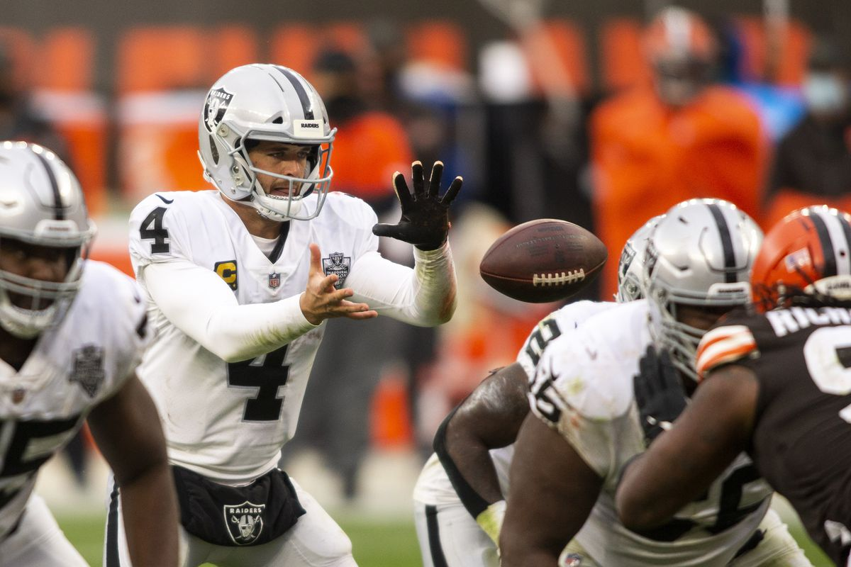 Las Vegas Raiders quarterback Derek Carr (4) reaches for the snapped ball against the Cleveland Browns during the third quarter at FirstEnergy Stadium.
