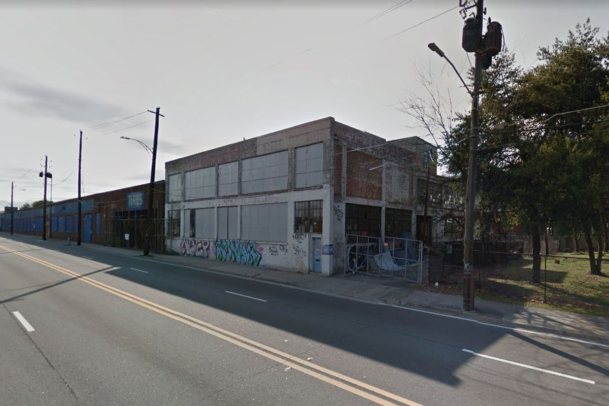A worn, two-story industrial building, with the MARTA Station directly behind.