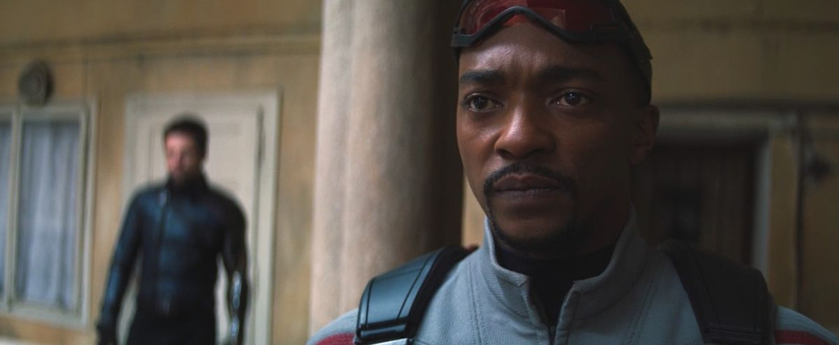 sam wilson up close in falcon gear with winter soldier behind him