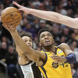 Utah Jazz guard Donovan Mitchell (45) shoots between San Antonio Spurs guard Derrick White (4) and San Antonio Spurs center Jakob Poeltl (25) during an NBA game at Vivint Arena in Salt Lake City on Friday, Feb. 21, 2020. The Jazz lost 104-113.