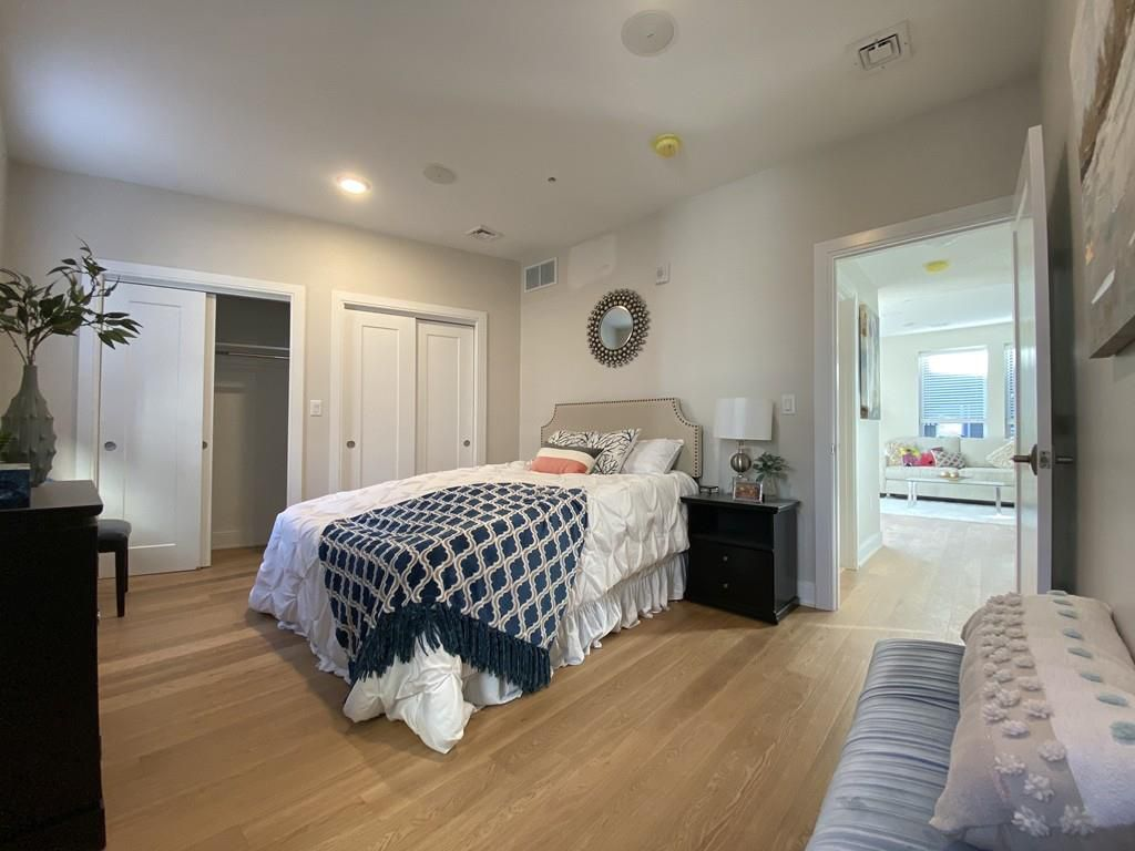 A bedroom with a bed and two couches.
