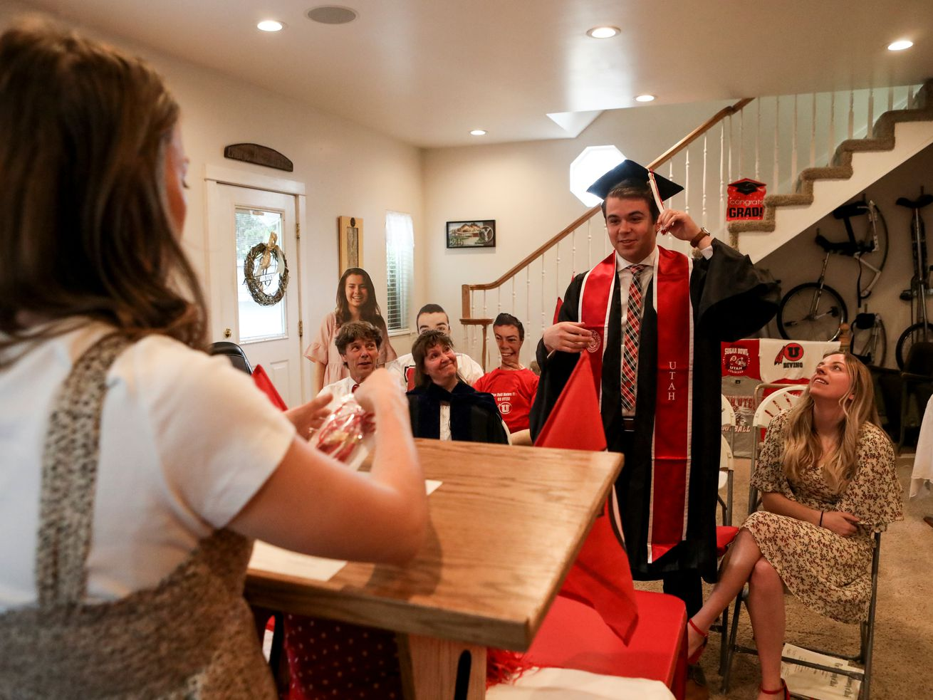 Ceciley Hallman Herod directs her brother Joseph Hallman to turn his tassel during a mock commencement ceremony in their parents' Sugar House home amid the COVID-19 pandemic on Thursday, April 30, 2020. Hallman earned bachelor's degrees in Latin American studies, Spanish and international business with an emphasis in trade commerce in 2019 with hopes of walking during the spring 2020 commencement ceremony.