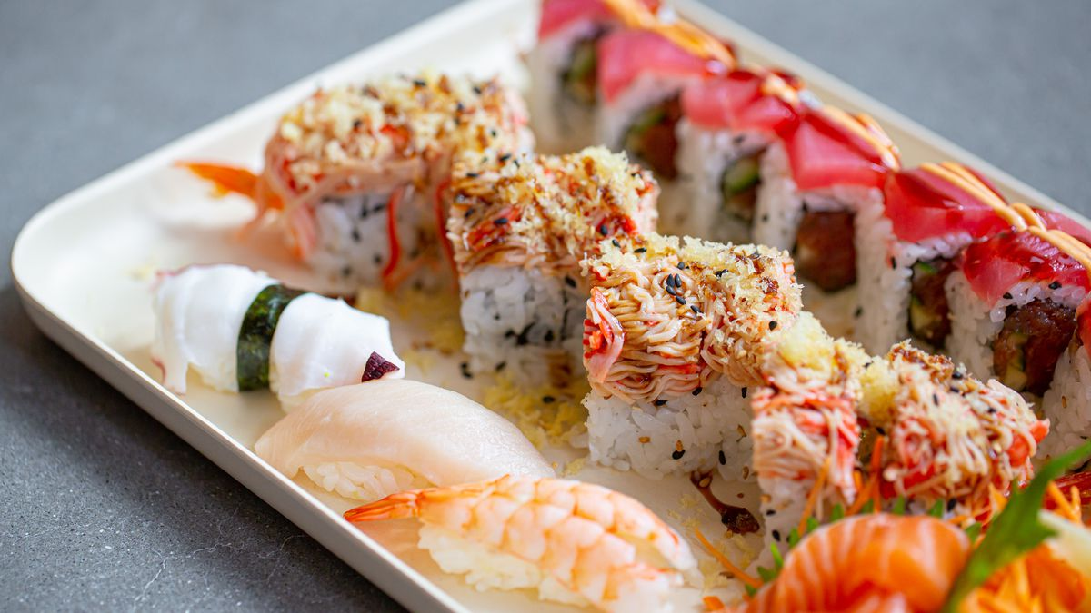 A white tray with sushi, sashimi, and rice