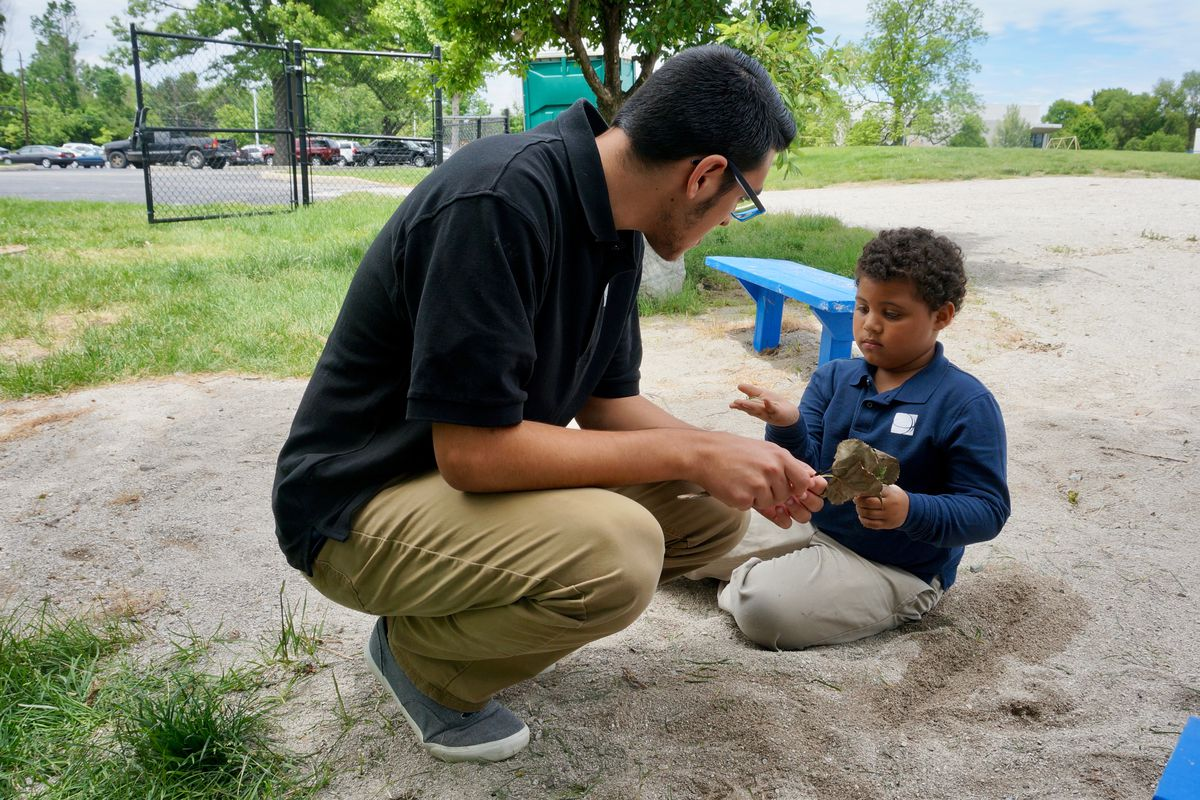 A teacher at Christel House Academy South works outside with a student.