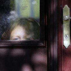 A child peers through the window on a door of Drew Peterson's house on Thursday, Sept. 6, 2012., in Bolingbrook, Ill. Retired Bolingbrook police officer Drew Peterson has been found guilty of murdering his third wife, Kathleen Savio. State's Atty. James Glasgow says he has not ruled out charging Peterson with the death of Peterson's fourth wife, Stacy, who has been missing since 2007.