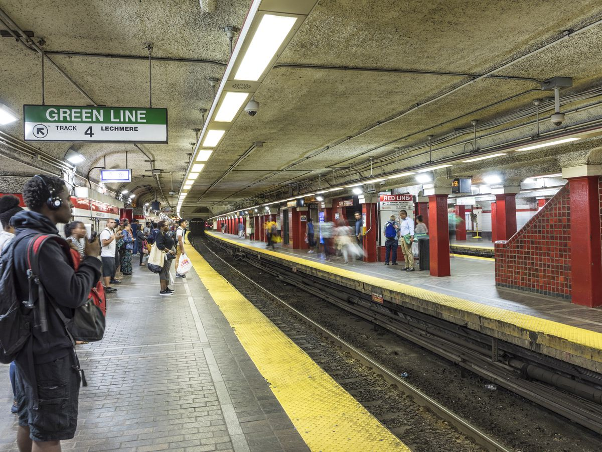 A subway platform with an empty train track and commuters awaiting the train.