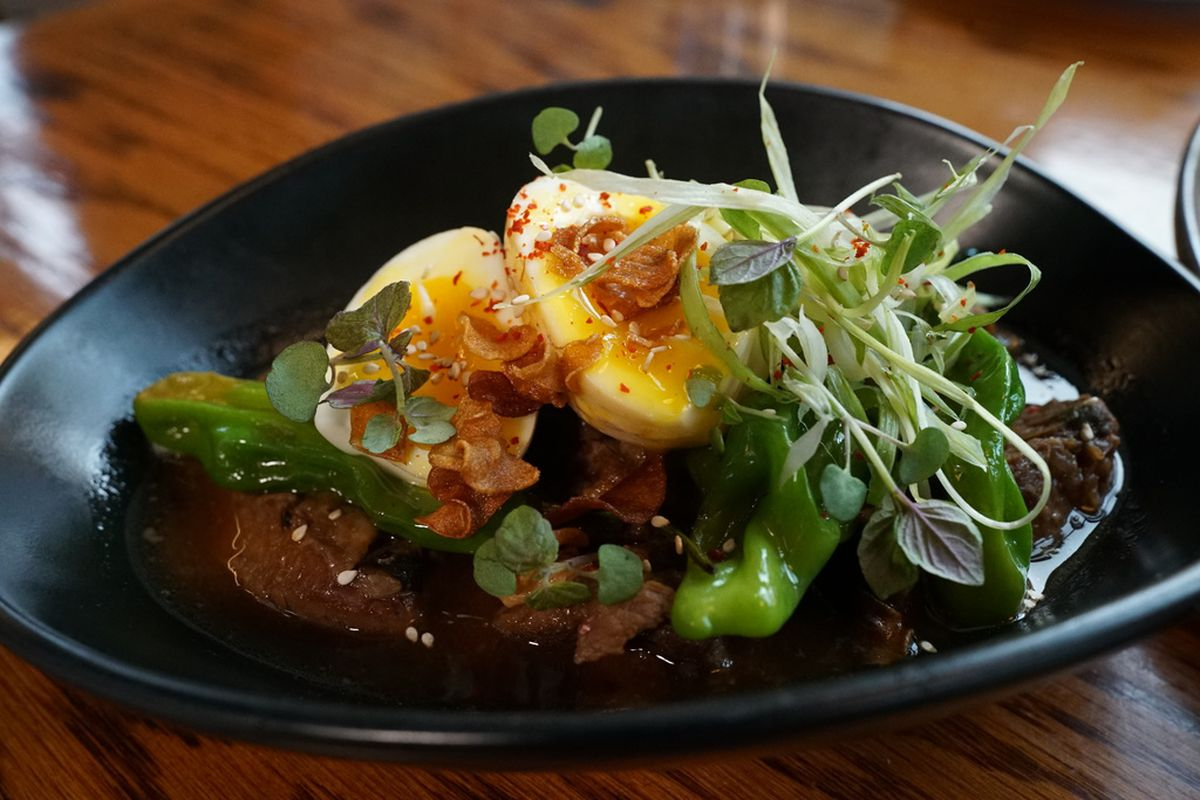 Braised beef with warm soy jus, served at Perilla, is made with shishito peppers, garlic, and a poached egg.