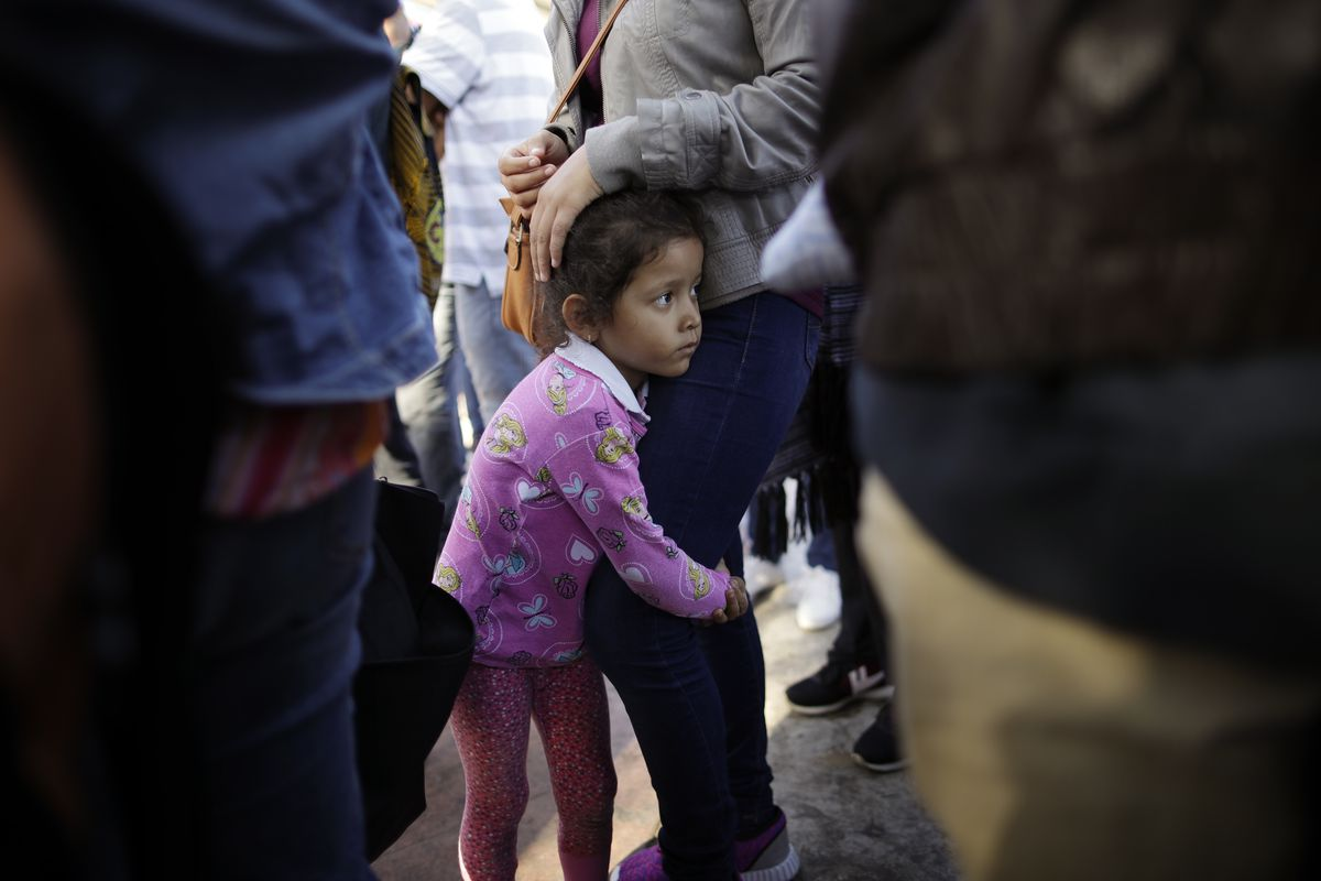 In this June 13, 2018 photo, Nicole Hernandez, of the Mexican state of Guerrero, holds on to her mother as they wait with other families to request political asylum in the United States, across the border in Tijuana, Mexico. The family has waited for abou