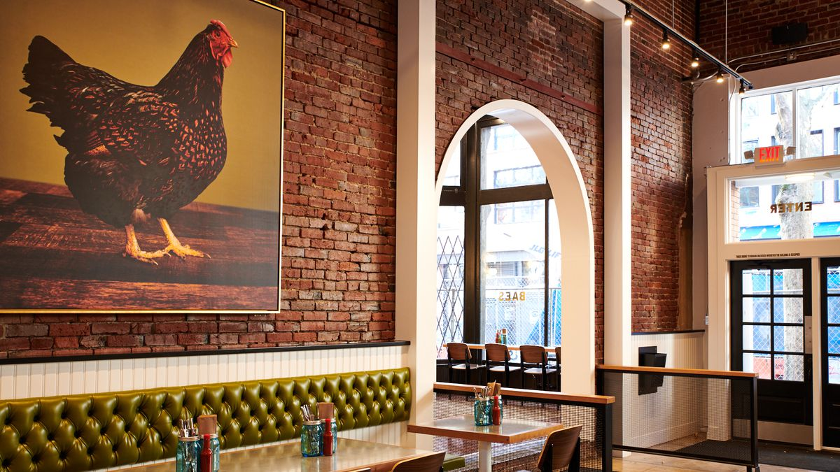A picture of a brown chicken is mounted on the wall of Bae's, over a green leather banquette