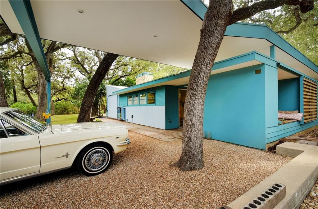 An outdoor photo of a midentury carport with a flat roof that zig zags on one side, apparently to get around the tree trunk in front of it. Some sort of sporty vintage car is parked on the gravel driveway underneath.